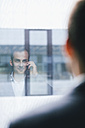 Reflection of businessman talking on phone on window pane - BZF000186
