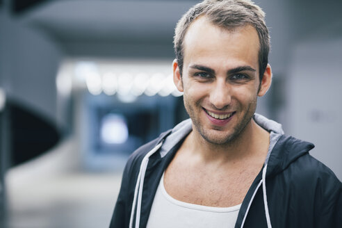 Portrait of smiling man wearing black hooded jacket - BZF000177