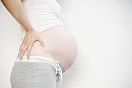 Close-up of pregnant woman holding her back - KRPF001617