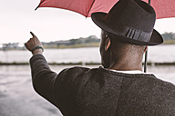 Young man with umbrella pointing his finger - STKF001369