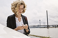 Young woman text messaging at the riverside - STKF001378
