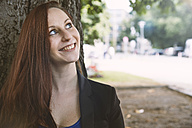 Smiling young woman leaning at tree looking up - STKF001390