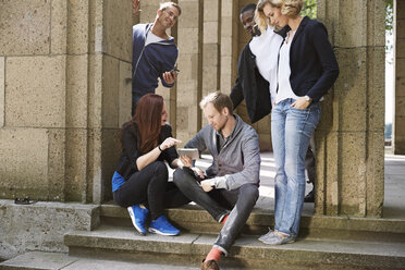 Group of friends outdoors sharing digital tablet - STKF001393
