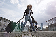 Woman on the phone walking with a rolling suitcase in the city - STKF001437