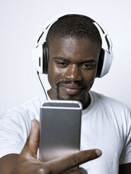 Smiling young man with headphones looking at cell phone - STKF001440