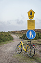 Germany, Sylt, Kampen, bicycle leaning on signs at beginning of nature reserve - KEB000240