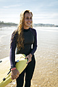 Spain, Colunga, portrait of smiling young woman with surfboard on the beach - MGOF000439