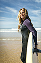 Spain, Colunga, smiling young woman with surfboard on the beach - MGOF000441
