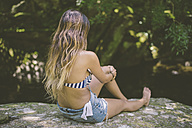 Back view of young woman sitting on a rock near river - RAEF000301