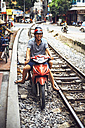 Vietnam, Hanoi, young man with motorbike on railway tracks - EH000138