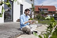Smiling man using digital tablet on terrace - RBF003461