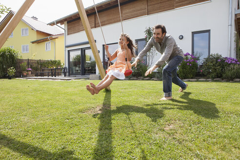 Father pushing daughter on a swing in garden - RBF003478