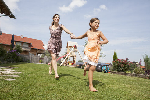 Carefree mother and daughter running in garden - RBF003436