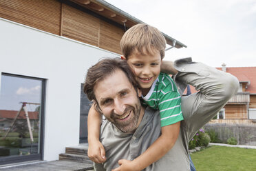 Portrait of happy father carrying son in garden - RBF003493