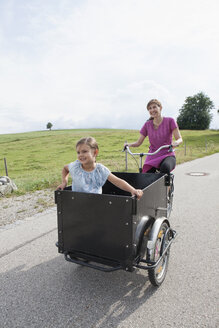 Mother riding bicycle with daughter in trailer - RBF003439