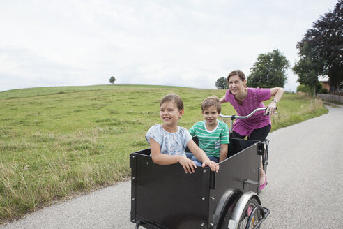 Mother riding bicycle with son and daughter in trailer - RBF003443