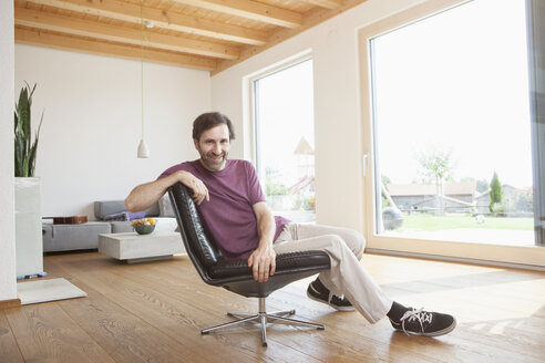 Mature man sitting relaxed in his living room - RBF003341