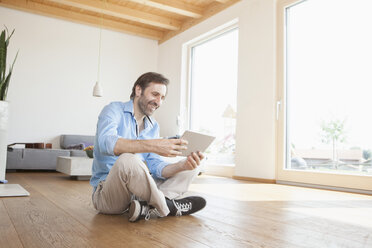 Mature man at home using digital tablet sitting on the floor - RBF003343