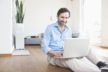 Mature man at home using laptop sitting on the floor - RBF003269