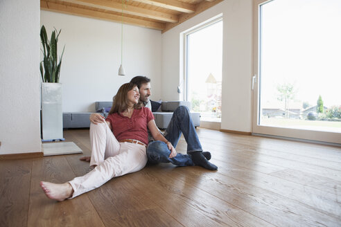 Mature couple sitting on floor, smiling happily - RBF003286