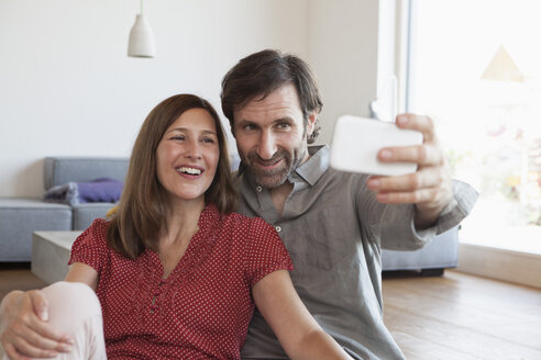 Mature couple sitting on floor taking selfie with smart phone - RBF003352