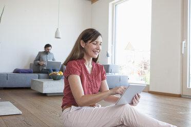 Mature woman using digital tablet on floor in living room, man using digital tablet in background - RBF003291