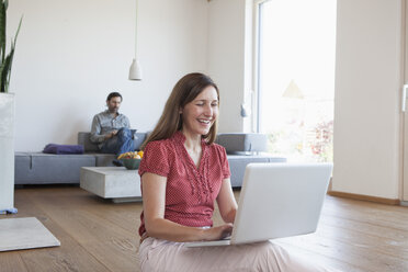Mature woman using laptop on floor in living room, man using digital tablet in background - RBF003292