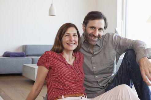 Mature couple sitting on floor of living room - RBF003294
