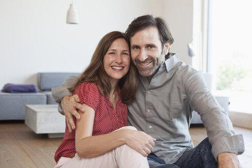 Mature couple sitting on floor of living room - RBF003295