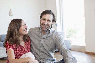 Mature couple sitting on floor of living room - RBF003297