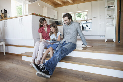 Happy family sitting on kitchen steps, parents reading book with daughter - RBF003361