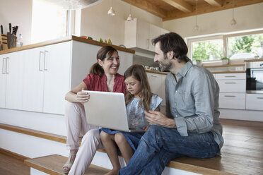 Happy family sitting on kitchen steps, daughter using laptop - RBF003310