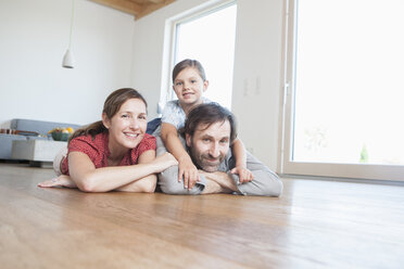 Happy family lying on floor, smiling - RBF003317
