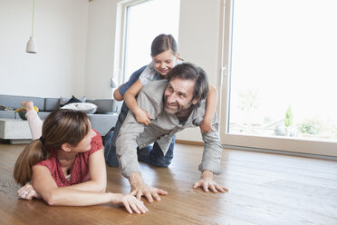 Happy family lying on floor, playing with daughter - RBF003318