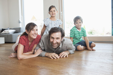 Happy family lying on floor, smiling - RBF003323