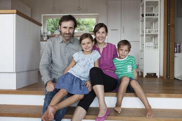 Happy family sitting on kitchen steps - RBF003325