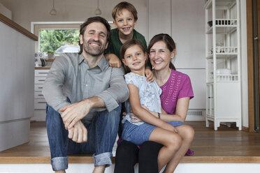 Happy family sitting on kitchen steps - RBF003365