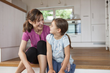 Mother and daughter sitting smiling in kitchen - RBF003336