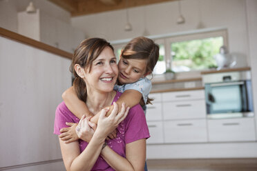 Mother and daughter sitting smiling in kitchen - RBF003337