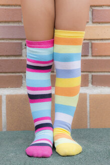 Feet of a girl with different striped colored socks - ERLF000007