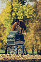 Father looking at his baby in pram in park on a sunny autumn day - CHAF001074
