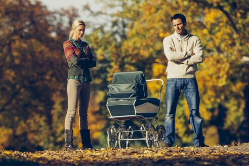 Reserved couple standing with crossed arms looking at baby carriage at autumnal park - CHAF001078