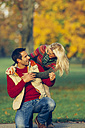 Happy couple in autumnal park - CHAF001159