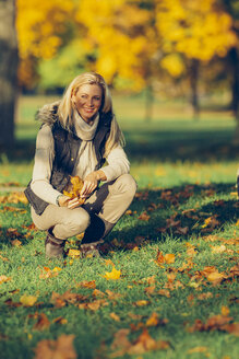 Woman crouching on a meadow in a park holding autumn leaves - CHAF001085
