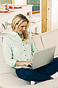 Smiling blond woman sitting on sofa using laptop - CHAF001261
