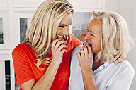 Smiling adult daughter with her mother eating vegetables - CHAF001099