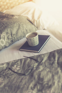 Book, reading glasses and cup of white coffee on bed - ASCF000317