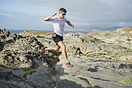 Spain, Valdovino, young man practicing trail running in a rocky landscape - RAEF000306