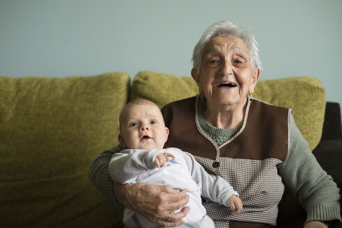 Portrait of great-grandmother sitting on a couch with her great-grandson - RAEF000310