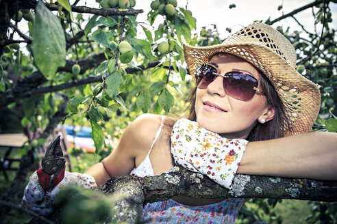 Portrait of smiling woman with gardening gloves and pruner leaning on branch - VTF000441